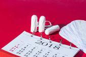 Fotografie Tampons, tägliche Liner und Kalender auf rot