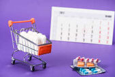 Fotografie tampons in small shopping cart, pills and calendar on purple