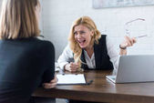 angry businesswoman screaming at coworker in office