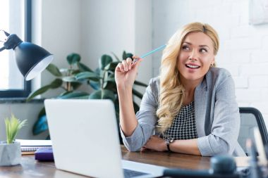 smiling businesswoman holding pencil and looking away at work