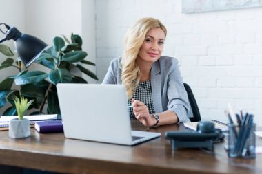 happy businesswoman sitting near laptop and looking at camera
