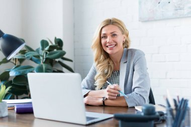 smiling businesswoman looking at camera in office