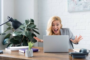 surprised businesswoman looking at laptop in office