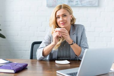 cheerful businesswoman holding cup of coffee in office and looking at camera