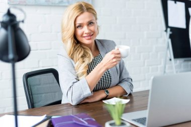 smiling businesswoman holding cup of coffee in office and looking at camera
