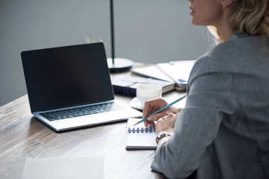 cropped image of businesswoman writing something to notebook with pencil in office