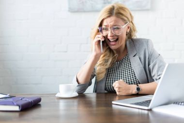 shocked screaming businesswoman talking by smartphone in office