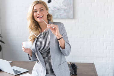smiling businesswoman holding cup of coffee and glasses
