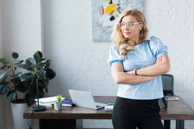 businesswoman standing with crossed arms and looking away