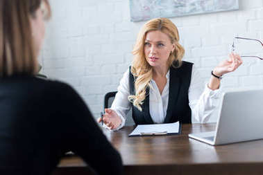 beautiful businesswoman talking with coworker in office