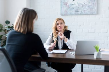 rear view of businesswoman talking with coworker in office