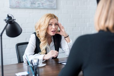 irritated businesswoman looking at coworker in office