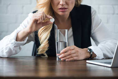 cropped image of businesswoman with pill and glass of water