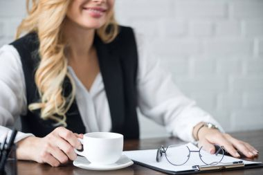 cropped image of businesswoman with cup of coffee