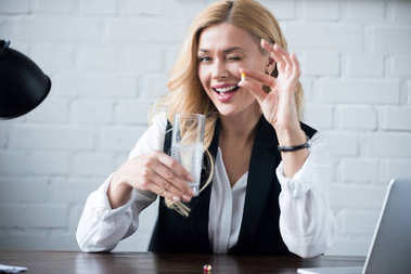 businesswoman winking and holding glass of water with pill