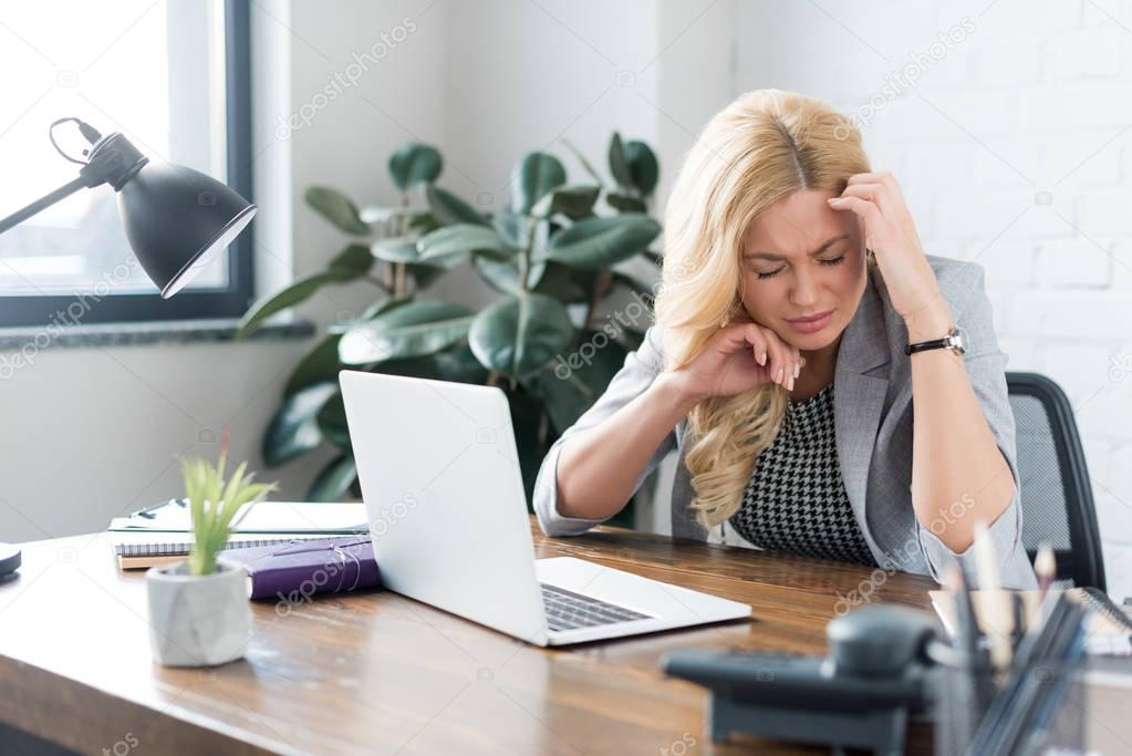 tired businesswoman having headache and touching head with hands