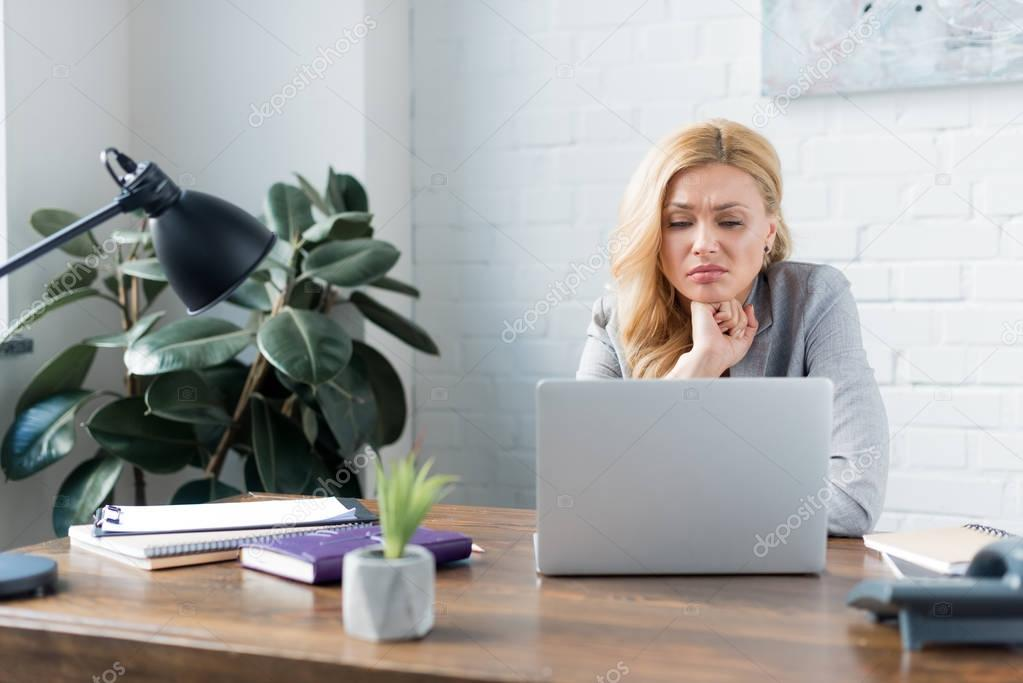 sad businesswoman looking at laptop in office