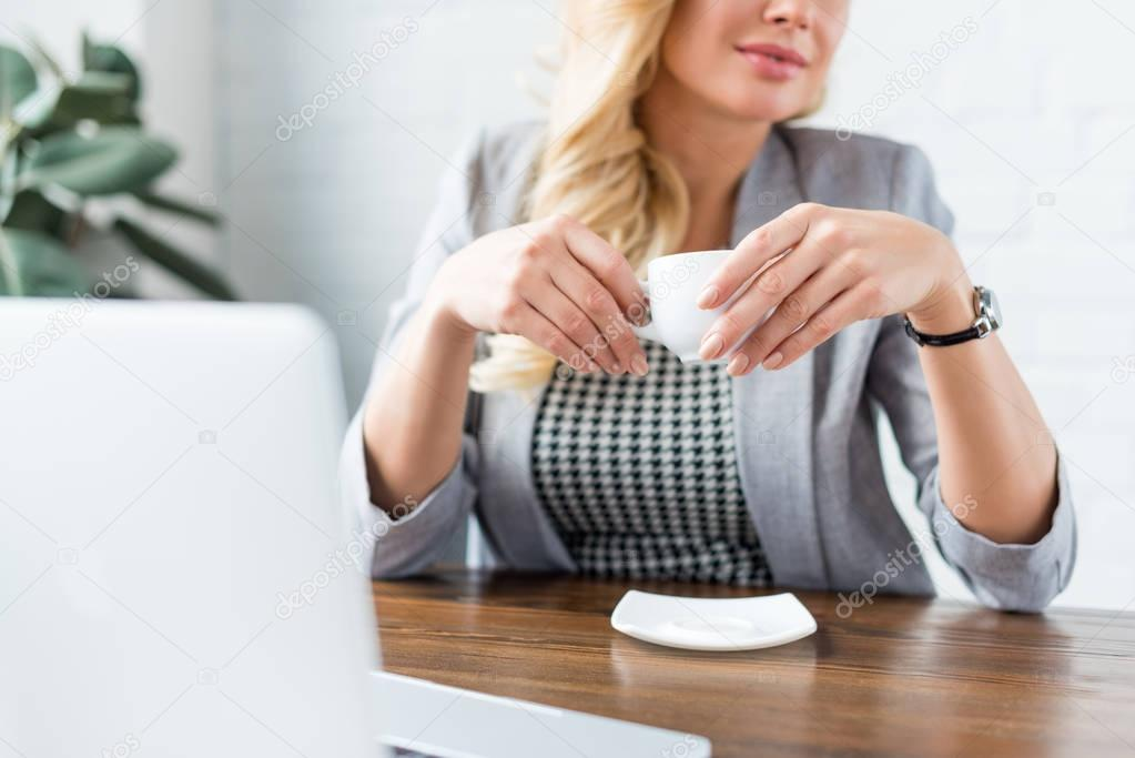 cropped image of businesswoman holding cup of tea at work