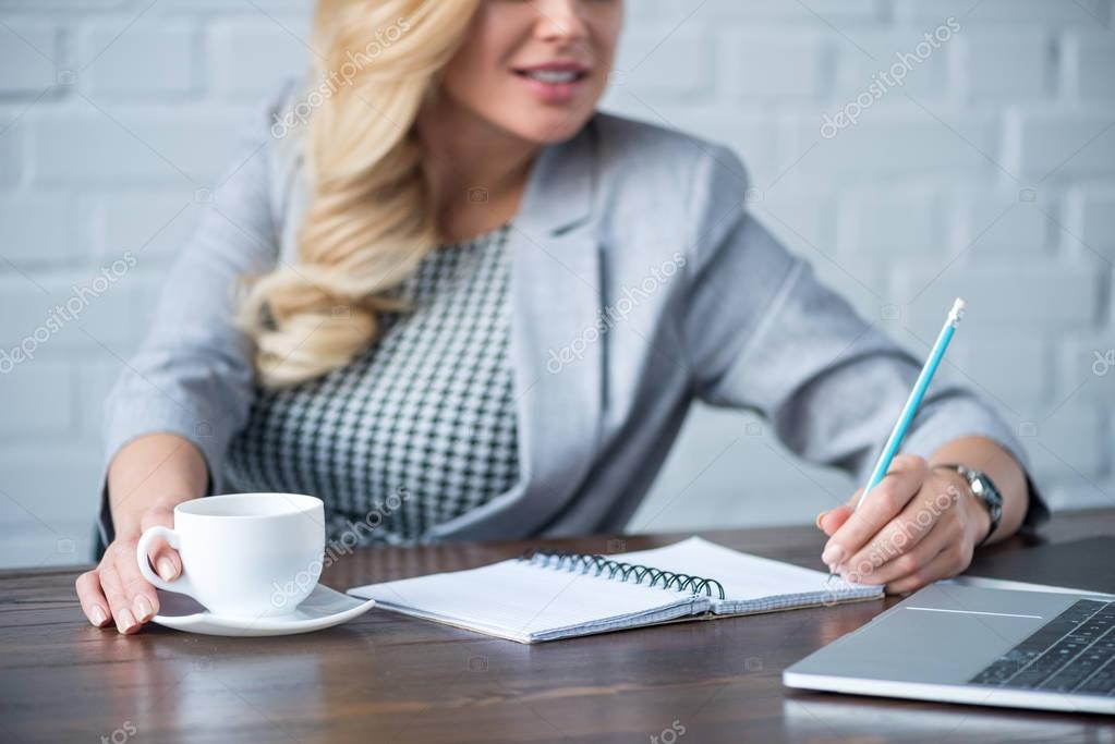 cropped image of businesswoman writing something to notebook and holding cup of coffee