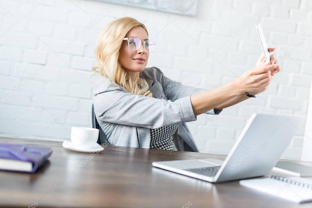 beautiful businesswoman taking selfie with smartphone in office