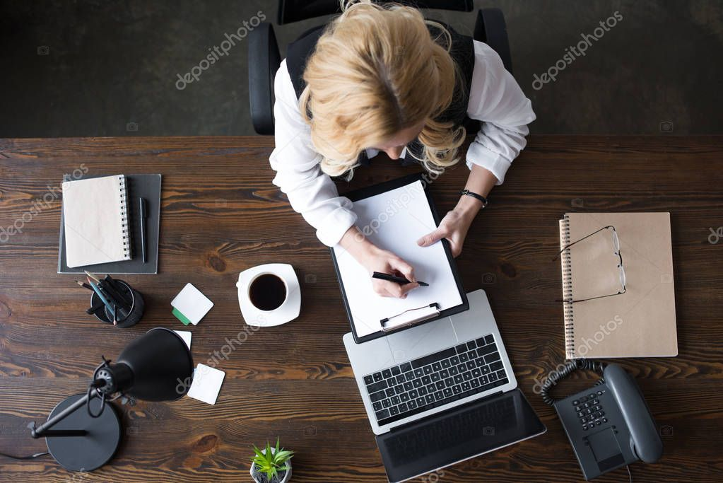 top view of businesswoman writing something to clipboard in office