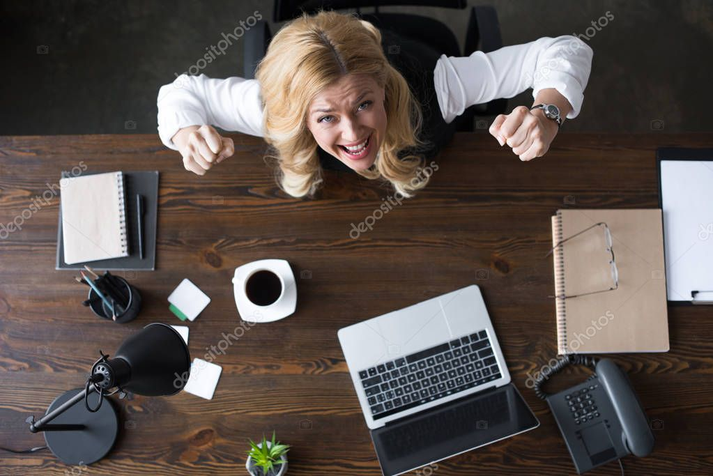 overhead view of businesswoman screaming and showing yes gesture in office