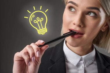 portrait of beautiful young businesswoman with pen and light bulb symbol, isolated on grey