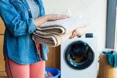 Fényképek levágott lövés a fiatal nő gazdaság halmozott tiszta törölközők otthon