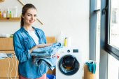 Fotografie mladá žena držící oblečení a usmívá se na kameru při stojící poblíž pračku doma