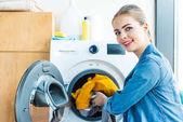 Fotografie mladá žena se usmívá na kameru při uvádění prádla do pračky