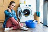 Fotografie krásná mladá žena se usmívá na kameru při sezení u pračky a plastové umyvadlo s prací