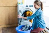 Lächelnde junge Frau, die Wäsche aus Waschmaschine in Plastikbecken bringt
