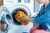 Fotografie oříznutý snímek mladé ženy dávat prádlo do pračky