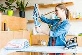 Fényképek szép mosolygó fiatal nő vasalás ruhát otthon
