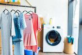 Fotografie Kleidung auf Kleiderbügeln und Waschmaschine zu Hause