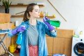 schöne junge Frau in Gummihandschuhen, die Plastikflaschen mit Reinigungsflüssigkeiten hält