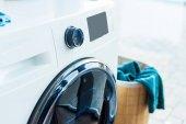Nahaufnahme von moderner Waschmaschine und Korb mit Wäsche zu Hause