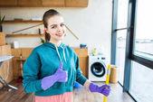 lächelnde junge Frau Hausputz mit Mop und Daumen auftauchen