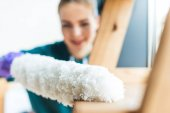 Fotografie close-up view of young woman with duster cleaning home