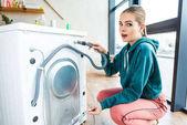 šokovaná mladá žena, zatímco krčí u rozbité pračky při pohledu na fotoaparát