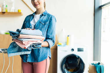 cropped shot of smiling young woman holding stacked clothes at home