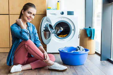 beautiful young woman smiling at camera while sitting near washing machine and plastic basin with laundry
