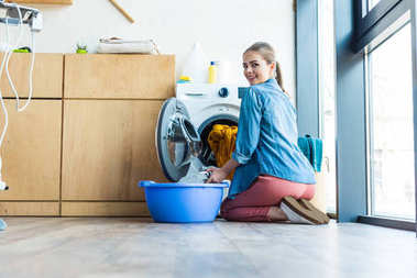 young woman taking laundry from washing machine and smiling at camera