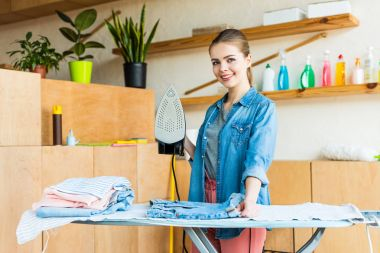 beautiful young woman holding iron and smiling at camera while ironing clothes at home