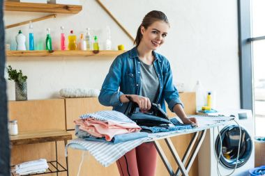 beautiful young woman ironing clothes and smiling at camera at home