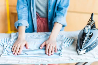 cropped shot of young woman ironing clothes at home