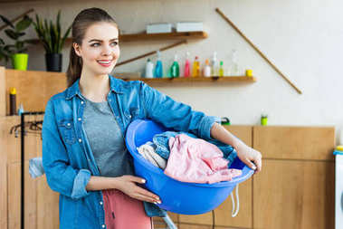 smiling young woman holding plastic basin with laundry and looking away