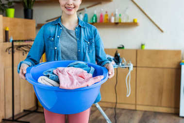 cropped shot of smiling young woman holding plastic basin with laundry