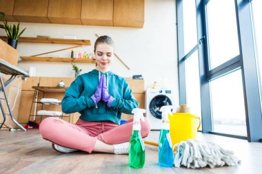 beautiful young woman sitting on floor and meditating while cleaning house