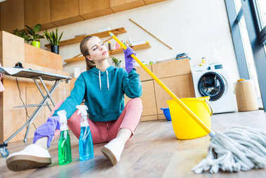 young woman in rubber gloves holding mop and sitting on floor while cleaning house